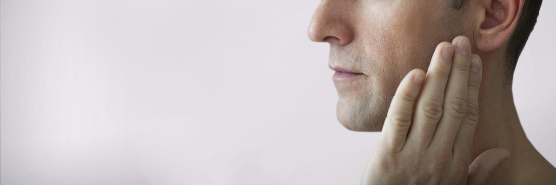Junger Mann mit Kiefergelenkbeschwerden